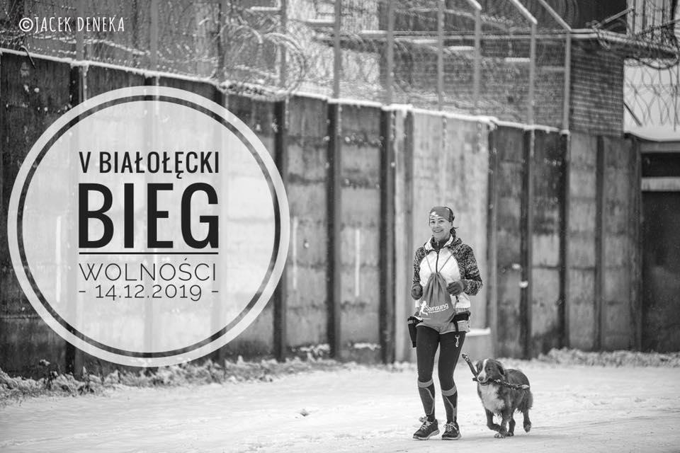 Biegnąca po śniegu uczestniczka zawodów. Obok biegnie pies trzymający w pysku patyk. W tle mur więzienny.